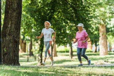 Selective focus cheerful senior women in sportswear jogging in park stock vector