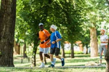 selective focus of happy multicultural men running with retired woman