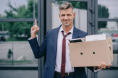 cheerful man in suit showing middle finger while holding box near building