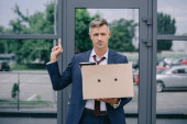 handsome man in suit showing middle finger while holding box near building