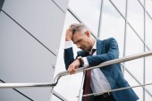 low angle view of frustrated businessman in formal wear standing outside near building