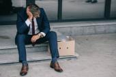 dismissed businessman sitting on stairs near carton box