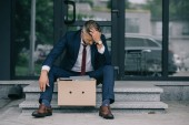 dismissed businessman sitting on stairs near carton box and touching hair