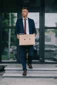 dismissed businessman walking on stairs near building and holding box