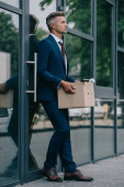 upset and fired businessman standing near building and holding carton box