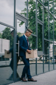 upset and fired businessman standing near building and looking at carton box