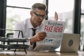 selective focus of emotional businessman in glasses gesturing while reading newspaper with fake news