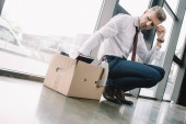 upset businessman looking at carton box in office