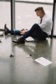 nespokojen muž gestikulací při sezení na podlaze a při pohledu na notebook