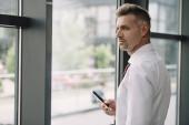 stattliche Mann hält Smartphone mit leerem Bildschirm in der Nähe von Fenster
