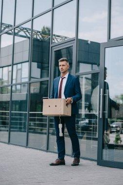 karton kutu ile binanın yanında duran kovulan işadamı