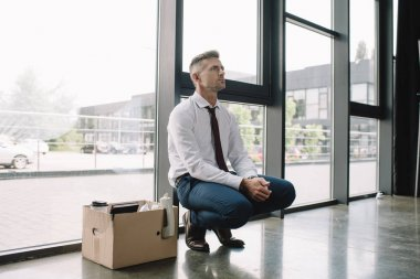 upset and fired man in suit sitting near carton box