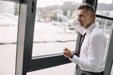 pencere yakınında duran takım elbiseli işadamı memnun değil