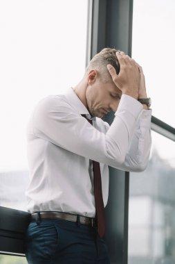 sad businessman touching hair while standing near windows