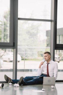 Pensive man holding pen while sitting on floor near laptop stock vector