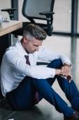 upset businessman sitting on floor near workplace in office