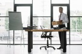 Photo dismissed businessman holding wooden box in modern office