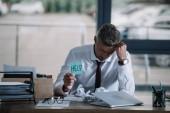 Aufgebrachter Geschäftsmann hält klebrigen Zettel mit Hilfe von Schriftzug am Tisch