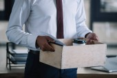 cropped view of dismissed man holding wooden box in office