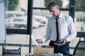 displeased businessman holding notebook and document near wooden box