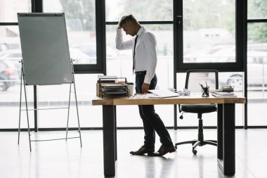 upset businessman touching head while standing near desk in office