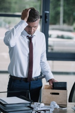 upset and dismissed businessman touching hair near box on table