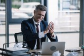 selective focus of angry businessman holding crumpled paper near laptop in office