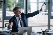angry businessman throwing in air smartphone with blank screen