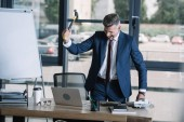 angry businessman holding hammer near laptop in office