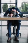 obchodník sedí nedaleko stolu s papírovým šálkem v moderní kanceláři