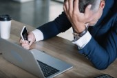 Photo selective focus of upset man in suit holding smartphone near laptop