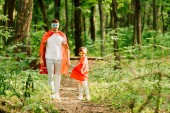 full length view of father and son standing in superhero costumes in forest