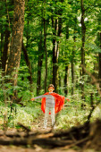 Fotografie selektivní zaměření malého chlapce v kostýmu superhrdiny a masky v lese