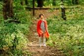 Fotografie pohled celé délky malého chlapce stojícího v kostýmu superhrdiny v lese na cestě
