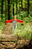 selective focus of small boy standing in superhero costume in forest and
