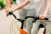 oříznutý pohled na chlapce přidržuje rukojeti jízdního kola, zatímco otec stál blízko syna