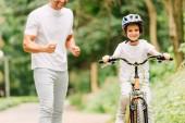 Fotografie Ausgeschnittene Ansicht von Vater jubelt Sohn zu, während Junge Fahrrad fährt und in Kamera schaut