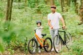 pohled plný délky otce a syna stojícího v lese s bicykly, zatímco muž křičel