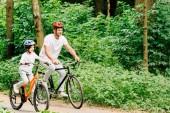 otec a syn se usmívají při jízdě na kolech kolem lesa