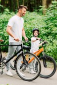 full length view of fahter and son standing with bicycles while boy looking at dad