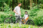 selektivní zaměření otce a syna na smích při stání s bicykly na silnici blízko lesa