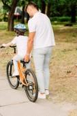 Fotografie pohled na otce, který pomáhal synovi jezdit na kole a přidržením jízdního kola