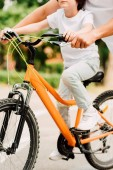 cropped view of boy riding bicycle and father holding handles of bike to help son