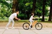 Fotografie boční pohled na povzbuzovat otce, zatímco dítě jede na kole