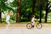 side view of happy father cheering son while kid riding bicycle