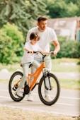 Fotografie pohled na otce, který se dívá dopředu a pomáhá synovi jezdit na kole, zatímco syn sedí na kole