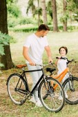 Ganzkörperansicht von Vater und Sohn mit Fahrrädern, die sich anschauen
