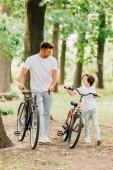 plný pohled na šťastného otce a syna, jak se na sebe dívají a usmívají se při chůzi s bicykly v lese