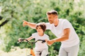 son riding bicycle while father helping kid and pointing with finger
