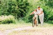 full length view of father helping son by holding handles of bike while son riding bicycle
